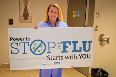 Gina Harding holds a flu campaign sign.