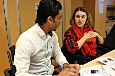 An Immigration Services Association of Nova Scotia employee chats with Haydar Al Shimmary, who moved to Canada from Iraq in June, about health concerns that could require a visit to the emergency department.