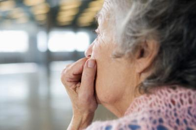 Senior woman looks out, appears lonely