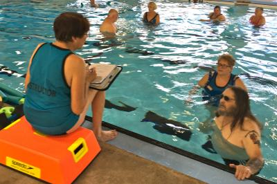 Valerie Wilson goes over exercises with Cliff Schneider and Fundy YMCA Volunteer Noelle Lucas.