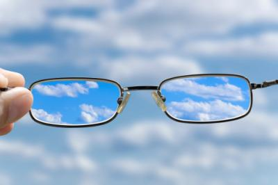 A photo of a pair of glasses sharpening a view of clouds