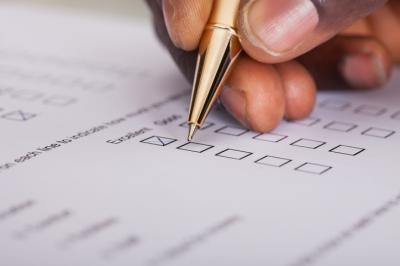 Hand completing paper survey