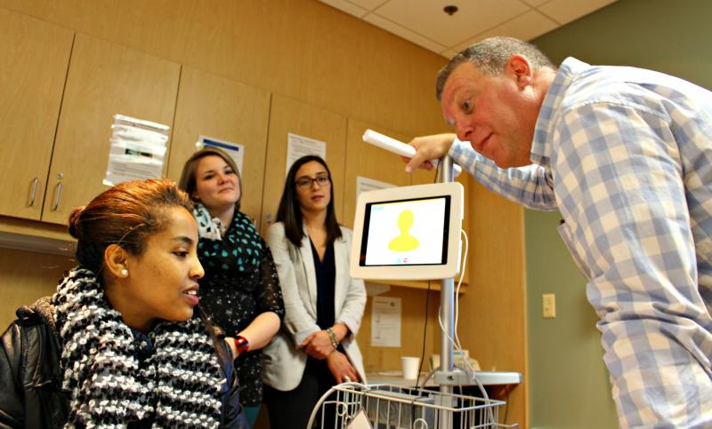 Robert MacKinley, health services manager at the Halifax Infirmary's emergency department, shows Immigration Services Association of Nova Scotia client Alsede Getashew how to use a virtual translator, a service added to the Halifax Infirmary about three m
